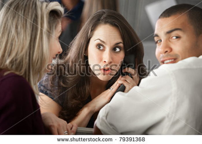 stock-photo-surprised-latina-office-worker-on-a-phone-call-as-co-workers-listen-79391368